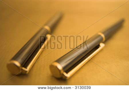 Two Pens On Gold Background