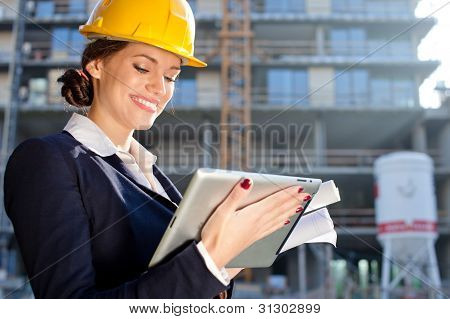 Attractive Female Construction Specialist With A Tablet Computer At Construction Site