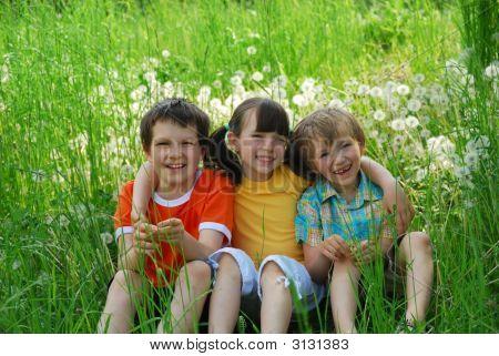 Children Sitting In Meadow