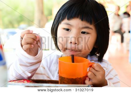 Little Asian Girl Holding Glass For Drink