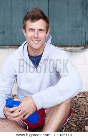 Portrait Of A Handsome Young Man Holding Water Bottle Outdoor