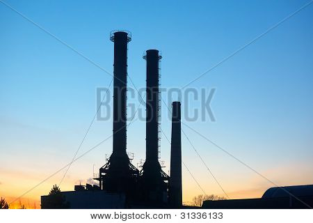 Factory pipes in the evening against blue sky