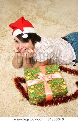 Girl Lying On The Carpet With Holiday Box