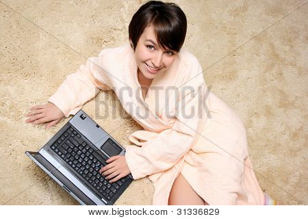 Happy Woman Lying On The Carpet With Laptop