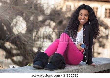 Portrait Of A Happy Young African American Teenage Girl Listening To Music