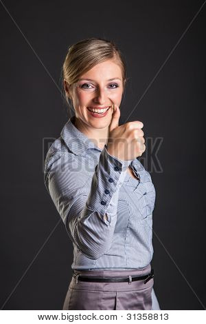 Businesswoman thumbs up on gray neutral background