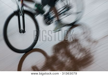Boy on bicycle reflecting in puddle
