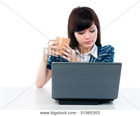 Young Female Holding Cup And Looking At Laptop