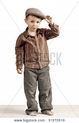 A little boy greets holding cap in his hand.