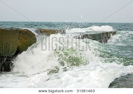 Wave crashing against the breakwater
