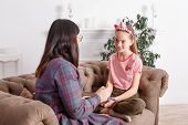 Mom And Daughter Are Sitting On The Couch And Chatting. Girl Teenager With Emotions Tells Her Mother poster