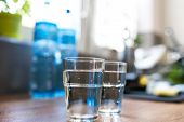 Two Glasses Of Water In Kitchen, With Tap Water And Two Bottles Of Mineral Water. Shallow Depth Of F poster