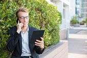 Smiling Positive Professional Working Outside. Young Business Man Sitting Outside, Using Tablet And  poster