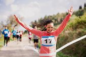Young Woman Runner Crossing Finish Line In A Race Competition In Nature. poster