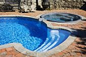 stock photo of paving stone  - Outdoor inground residential swimming pool in backyard with hot tub - JPG