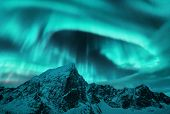 Aurora Borealis Above The Snow Covered Mountain Peak In Lofoten Islands, Norway. Northern Lights In  poster