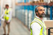 Side view of thoughtful mature Asian male worker looking away in warehouse. This is a freight transp poster