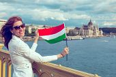 Happy Young Redhead Hungarian Urban Woman Stretching Hungarian Flag At Budapest poster