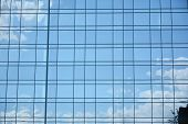 Geometric Reflection: Partly Cloudy Sky Reflected By Window Panes Of Office Building poster