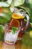 stock photo of iced-tea  - iced tea with lemons and a glass with ice cubes and mint - JPG