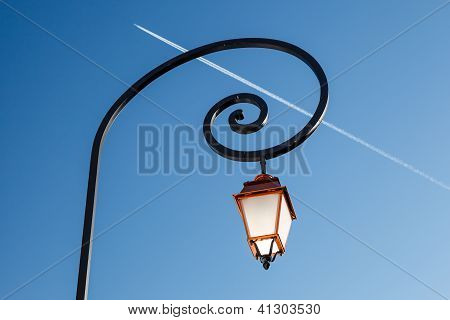 Shining Backlit Streetlamp And Airplane Trail In Background, Megeve, France