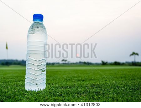 Drinking Water Bottle On Green Field