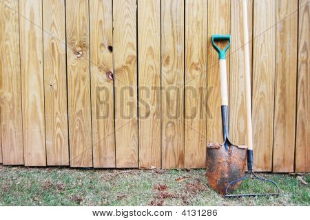 Shovel And Rake Leaning On Fence