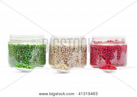 Red, Green And White Peppercorns On Spoons Isolated On A White Background