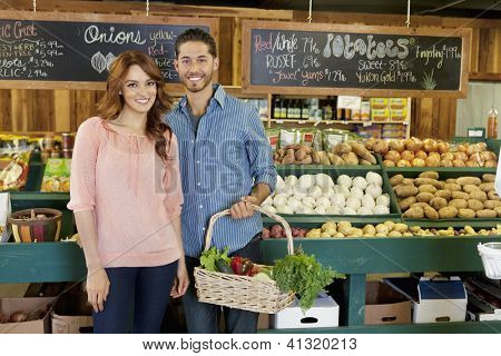 Happy young couple in vegetable market