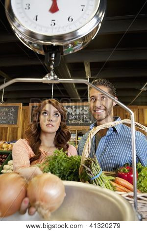 Happy young couple looking at weight scale in supermarket