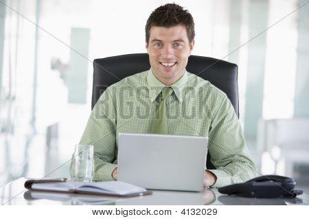 Empresario sentado en la oficina con Organizador Personal utilizando Laptop sonriendo