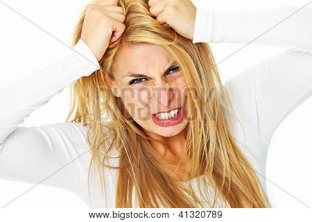 A picture of a young depressed woman tearing out her hair over white background