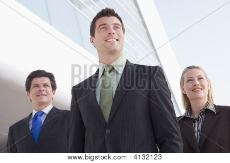 Three Businesspeople Standing Outdoors By Building Smiling