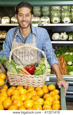 Retrato de un hombre feliz con la situación de la canasta de verduras cerca de parada de naranjas en supermercado