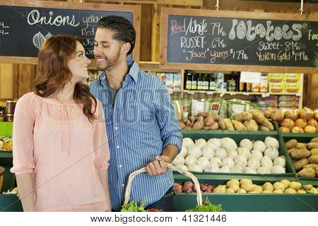 Happy young couple shopping together for vegetables in market