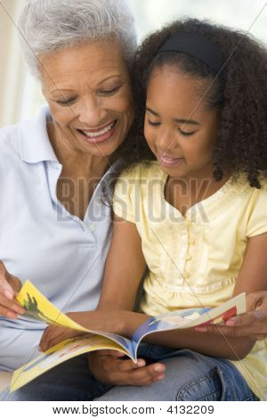 Grandmother And Granddaughter Reading And Smiling