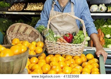 Midsection of man standing near oranges stall with vegetable basket in supermarket