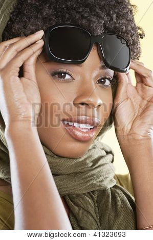 Portrait of an African American woman holding sunglasses with a stole round her neck over colored background