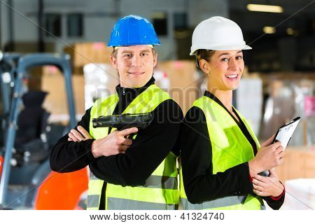 Teamwork- Worker or warehouseman with scanner and his coworker with clipboard at warehouse of freight forwarding company