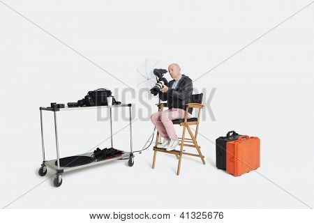 Middle age photographer looking at camera while sitting on director's chair in studio