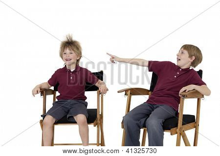Preteen boy pointing at friend's hair while sitting on director's chair over white background