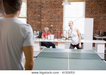 Man And Woman In Office Space Playing Ping Pong