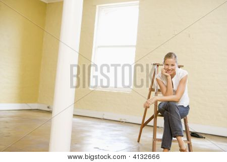 Woman Sitting On Ladder In Empty Space Smiling