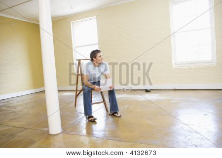 Man Sitting On Ladder In Empty Space Holding Paper Smiling