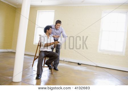 Two Men With Ladder In Empty Space Looking At Paper