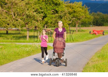 Family sport - mother and daughter jogging down a path with a baby stroller at a wonderful sunny day