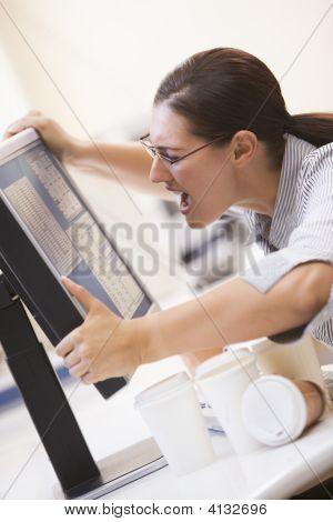 Frau in Computer-Raum ihr Monitor greifen und schreien