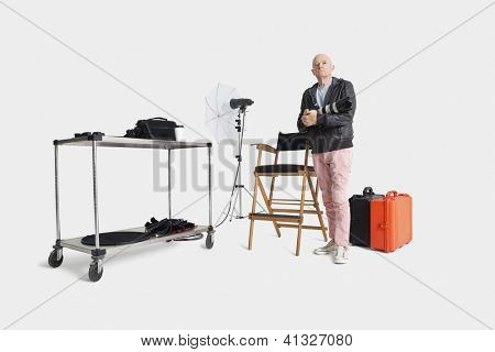 Middle age man with camera and equipments standing in photographer's studio