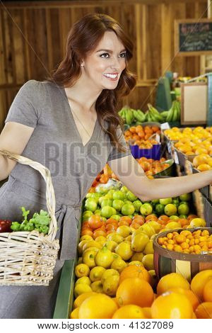 Happy young woman shopping in supermarket for fruits
