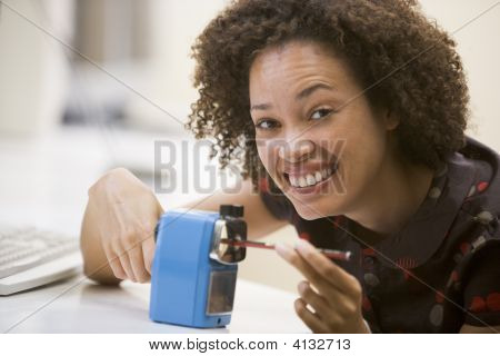 Woman In Computer Room Using Pencil Sharpener And Smiling